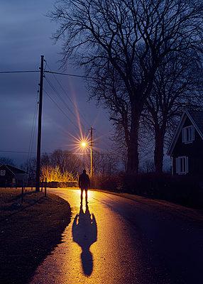 Mann im Licht der Straßenlaterne - p1124m1193543 von Willing-Holtz
