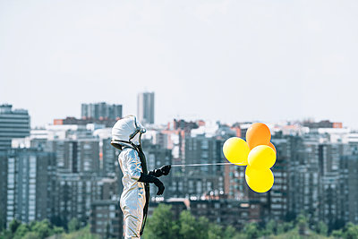 Boy dressed as an astronaut holding balloons in the city - p300m2140088 by Jose Luis CARRASCOSA