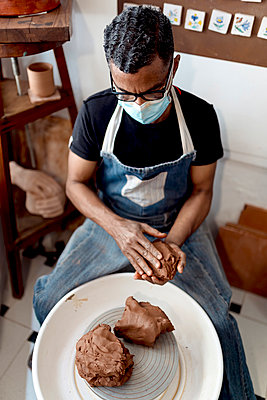 Male potter wearing mask holding clay while sitting in workshop - p300m2213960 by Ezequiel Giménez