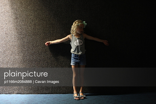 little girl in shadows against dark wall in shorts - p1166m2084888 by Cavan Images