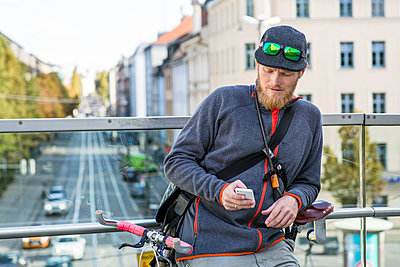 Bike messenger looking at smartphone - p1026m1187625 by Patrick Frost