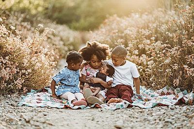 Four happy siblings sitting on blanket in backlit field together - p1166m2162629 by Cavan Images