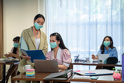 Asian business people wear protective face mask due covid workin - p1166m2246631 by Cavan Images