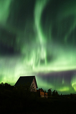 Iceland, Northern lights over a building - p1643m2229352 by janice mersiovsky