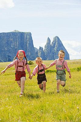 Italy, Seiseralm, Three children (4-5), (6-7), (8-9) running in field - p3008658f by Westend61
