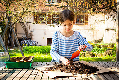 Girl filling nursery pots with soil and seeds - p300m2180924 by Larissa Veronesi
