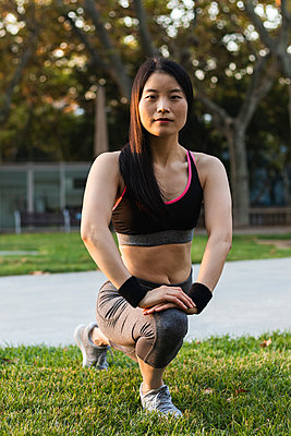 Determined woman exercising on grass in park - p300m2243970 by NOVELLIMAGE