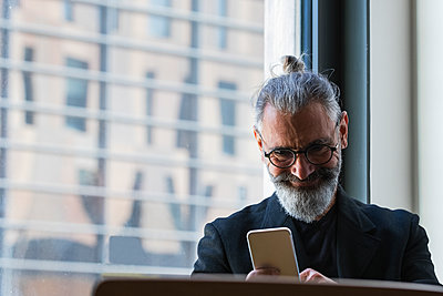 Smiling male entrepreneur working on mobile phone in coffee shop - p300m2277346 by NOVELLIMAGE