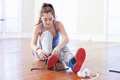 Teenage girl tying trainer laces in ballet school - p924m975780f by Chris Baldwin