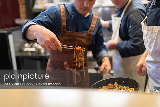 Cropped chef serving pasta near colleagues - p1166m2250633 by Cavan Images