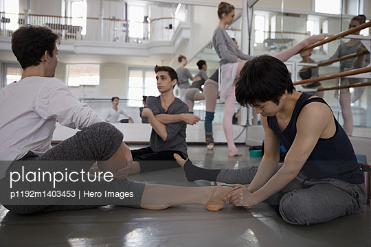 Male ballet dancers stretching, warming up in dance studio