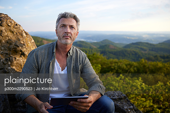 Male hiker sitting with digital tablet on top of mountain - p300m2290523 by Jo Kirchherr