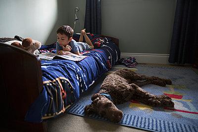 Dog sleeping floor below boy reading book bed - p1192m1078231f by Hero Images