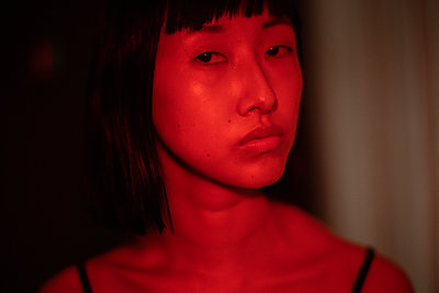 Asian woman bathed in red light - p1321m2211716 by Gordon Spooner