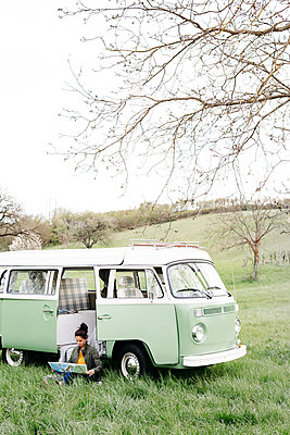 Young woman studying map, sitting in the grass, in front of her camper - p300m2114400 von Epiximages