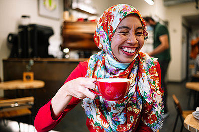 Woman in floral hijab laughing while holding coffee cup at cafe - p300m2240877 by Jose Luis CARRASCOSA
