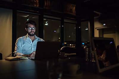 Mid adult businessman in office at night typing on laptop - p429m2091529 by Eugenio Marongiu