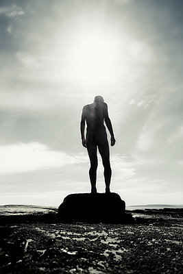 Naked man standing on rock at seaside - p597m1589909 by Tim Robinson
