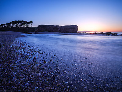 Sunrise behind the silhouetted cliff of Otter Head, where the River Otter meets the sea at Budleigh Salterton, Devon, England, United Kingdom - p871m2075315 by Baxter Bradford