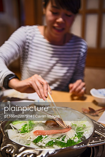 Woman eating seafood at restaurant in Kyoto - p1166m2207914 by Cavan Images