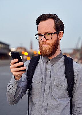 Mann mit Smartphone in der Dämmerung - p1124m1169983 von Willing-Holtz