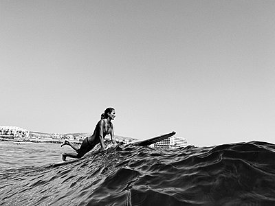 Full length of a female surfer on her longboard, black and white - p1166m2108277 by Cavan Images