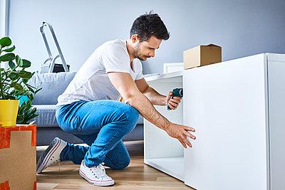 Man assembling a bookshelf in new apartment - p300m1588029 by Bartek Szewczyk