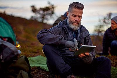 Hiker using digital tablet by tent, Keimiotunturi, Lapland, Finland - p429m1187953 by Aleksi Koskinen