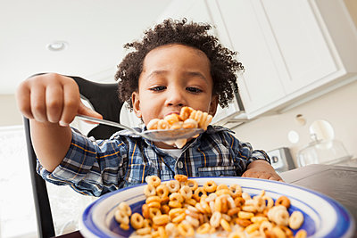 Mixed race boy eating at table - p555m1464118 by Mike Kemp