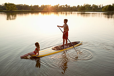 Children on paddleboard on lake - p555m1479666 by King Lawrence