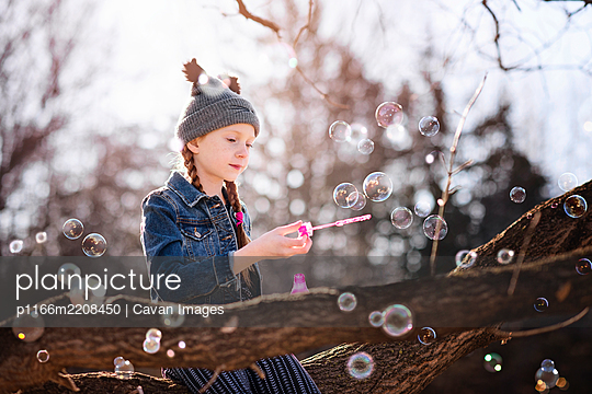 Young Girl Blowing Bubbles Outdoors in Fall - p1166m2208450 by Cavan Images