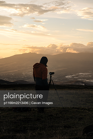 Photographer taking photos in the mountains with yellow sunset - p1166m2213496 by Cavan Images