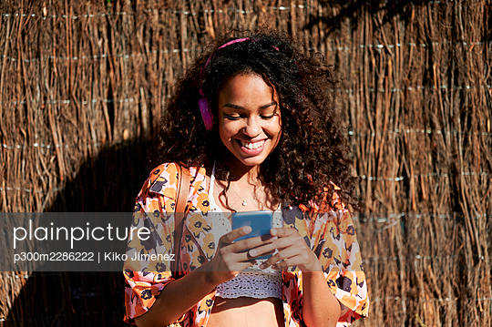 Spain, Andalusia, Jerez, portrait of woman with headphones and mobile phone outdoors. - p300m2286222 von Kiko Jimenez