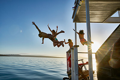Young adult friends jumping from summer houseboat into sunny ocean - p1023m1217944 by Francis Pictures