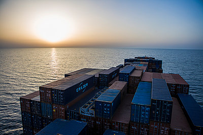 Container ship at setting sun - p1157m1041438 by Klaus Nather