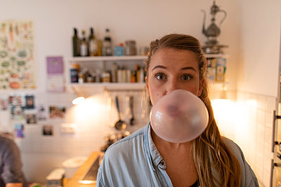 Young woman in kitchen at home making chewing gum bubble - p300m2131935 by Gustafsson