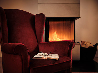 Eyeglasses with open book on maroon wingback chair by fireplace at home - p300m2250916 by Dirk Kittelberger
