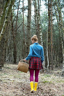 Young woman with basket in the forest - p427m1333070 by R. Mohr