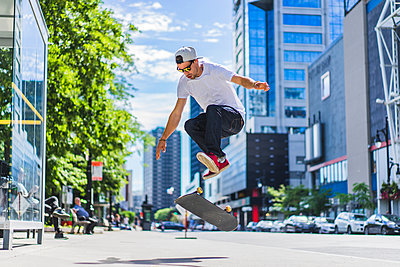 Skateboarder on street in town centre, Montreal, Quebec, Canada - p924m1224636 by Charles Knox
