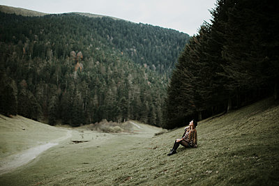 Young woman sitting on a meadow near forest edge looking up - p300m1550055 by Oriol Castelló Arroyo