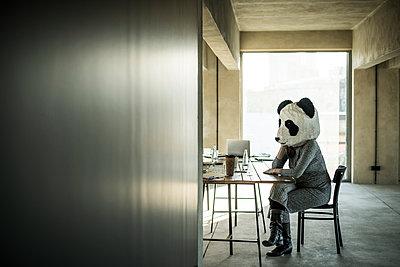 Woman with panda mask sitting in office, thinking - p300m2104107 von Malte Jäger