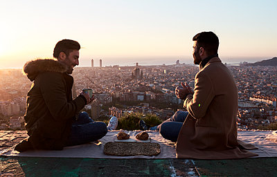 Gay couple having breakfast on observation point during sunrise, Bunkers del Carmel, Barcelona, Spain - p300m2256682 by Veam