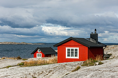 Wooden houses on coast - p312m1114047f by Henrik Trygg