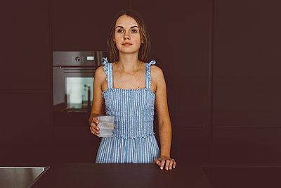 Nachdenkliche junge Frau in der Küche - p432m2203199 von mia takahara