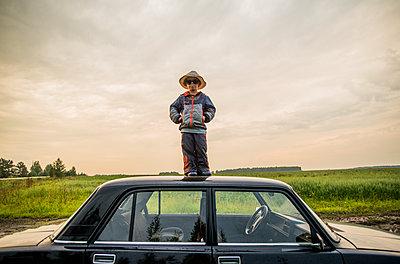 Caucasian boy standing on car roof in rural field - p555m1420568 by Aleksander Rubtsov