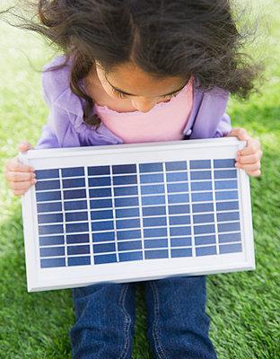 Mixed race girl holding solar panel - p555m1479096 by JGI/Jamie Grill