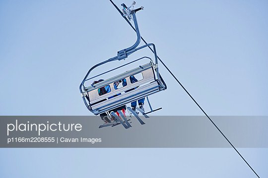 Skiers on a chairlift looking down with a blue background - p1166m2208555 by Cavan Images