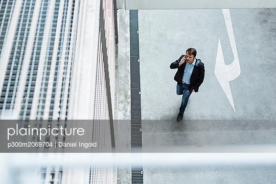 Businessman walking in parking garage, using mobile phone - p300m2069704 by Daniel Ingold