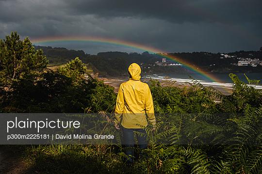 Rear view of woman wearing raincoat during rainy season - p300m2225181 by David Molina Grande