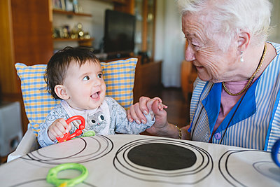 Great-grandmother playing with a baby girl sitting in the high chair next to the table with toys - p300m1459932 by Gemma Ferrando